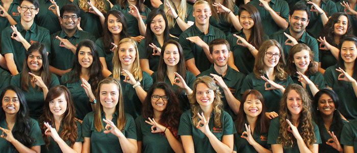 A group of UTD students making the UTD 'Whoosh' hand symbol.